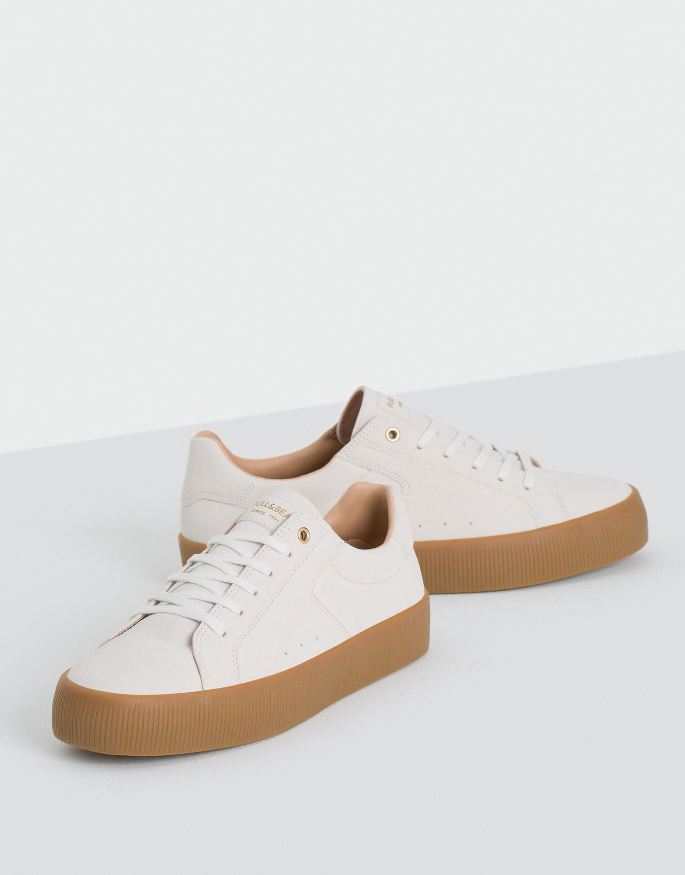 White plimsolls with caramel sole