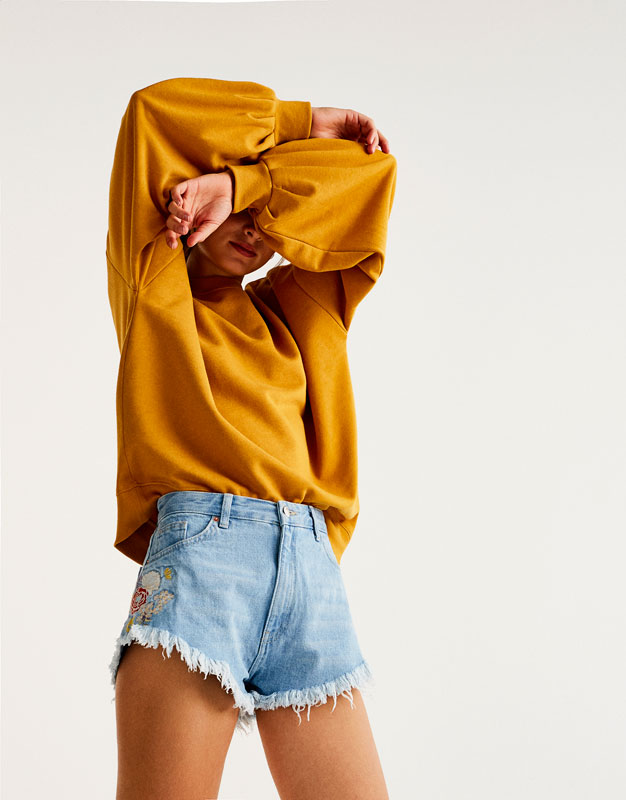 Denim shorts with floral embroidery and frayed hems