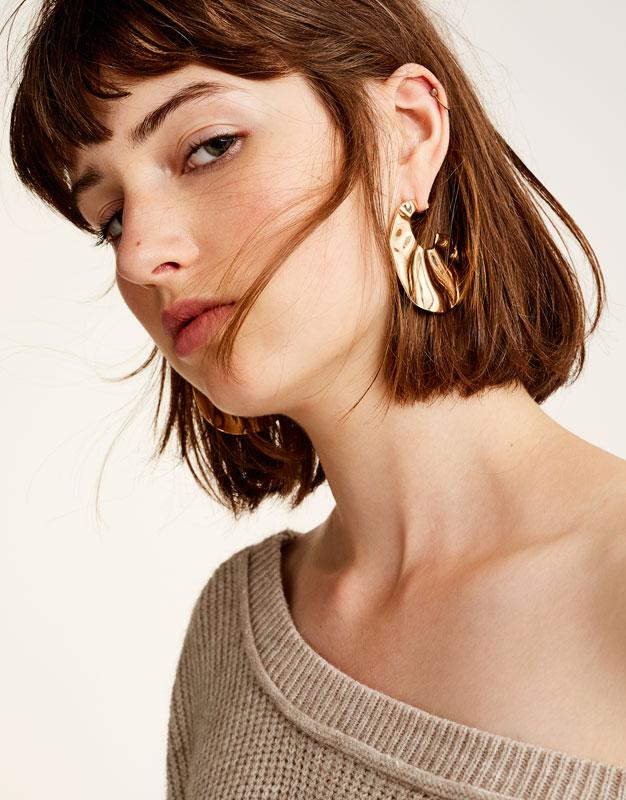 Goldfarbene Ohrringe mit Wellen