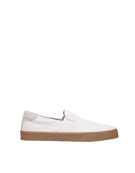 Weißer Sneaker mit karamellfarbener Sohle.