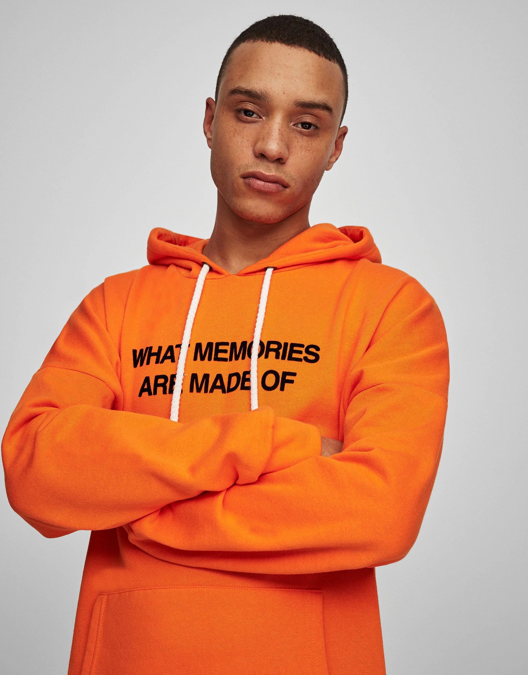 Orange hooded sweatshirt with slogan