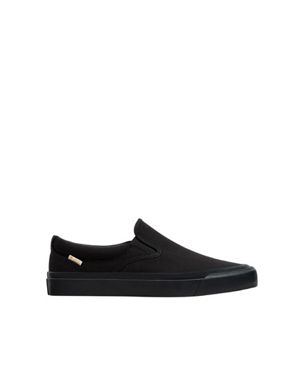 Black plimsolls with elastic tabs