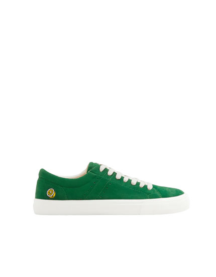 Green trainers with patch on heel