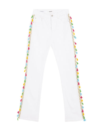 Flared jeans with multicoloured tassels