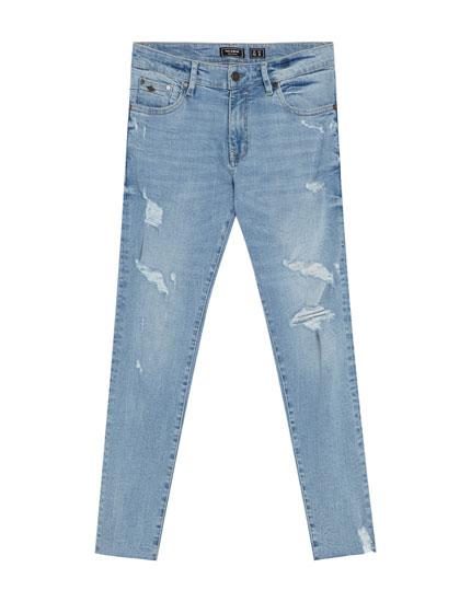 Džinsi 'skinny fit' gaiši zilā krāsā ar plēsumiem