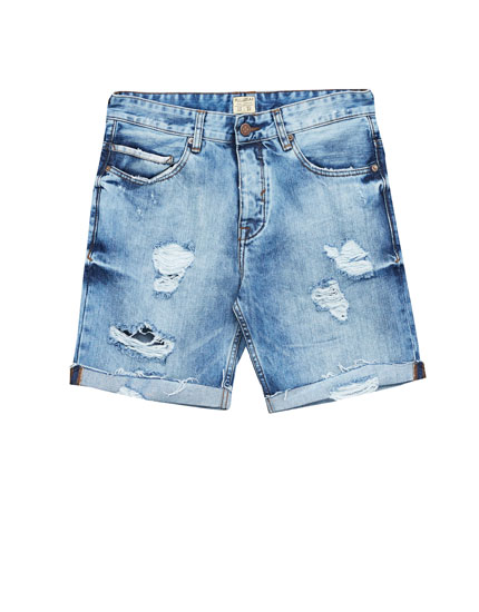 Ripped denim bermuda shorts with rolled-up hems