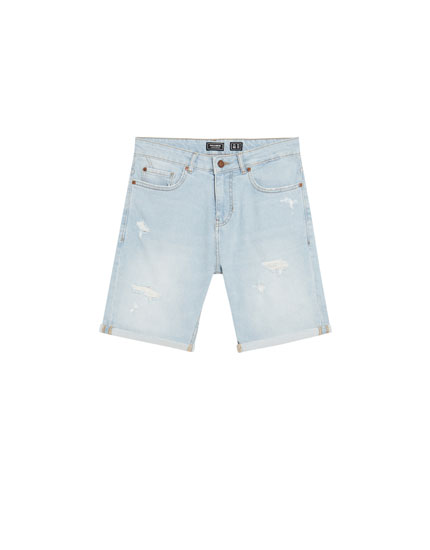 Slim fit bleached denim Bermuda shorts with ripped details