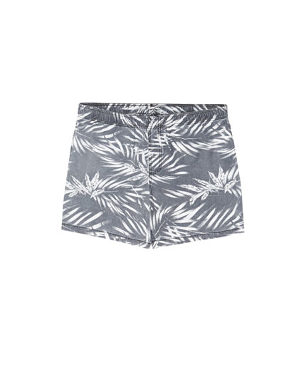 Faded-effect swimming trunks with palm tree print