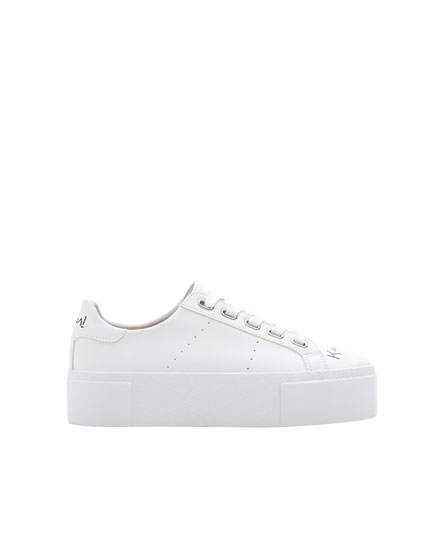White chunky sole sneakers with slogan