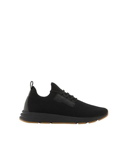 Schwarze Sneaker mit Gittermuster und elastischem Schaft
