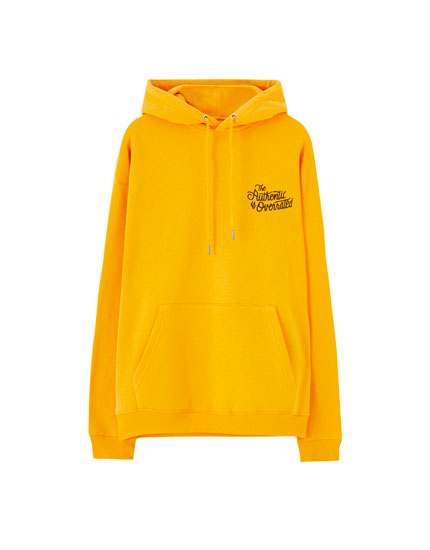 Mustard yellow hoodie with contrast slogan