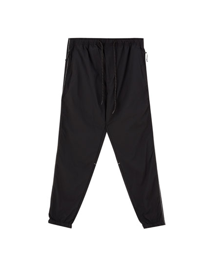 Black trousers with reflective piping