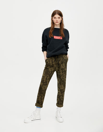 Camouflage jogging trousers with rolled-up cuffs