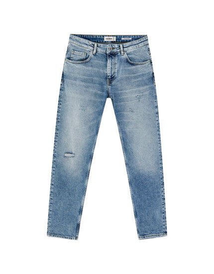 Slim fit tapered jeans with distressed finish