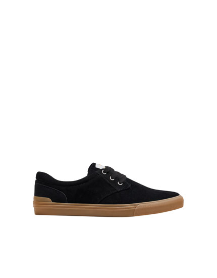 Black trainers with die-cut detailing