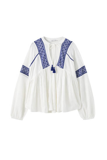 White loose-fitting blouse with contrast embroidery