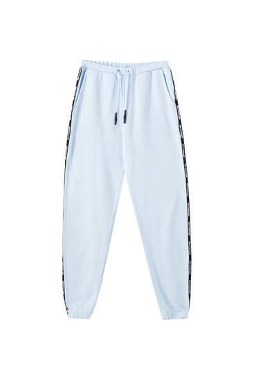 Jogging trousers with stripe and slogan