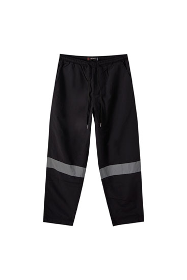Technical trousers with reflective strips