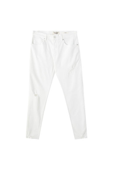 White skinny jeans with rips on the legs