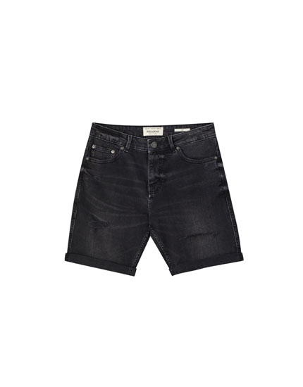 Faded black Bermuda shorts with rips