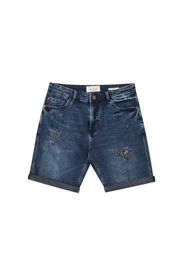 Faded dark blue Bermuda shorts with rips