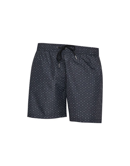 Black swimming trunks with a geometric print
