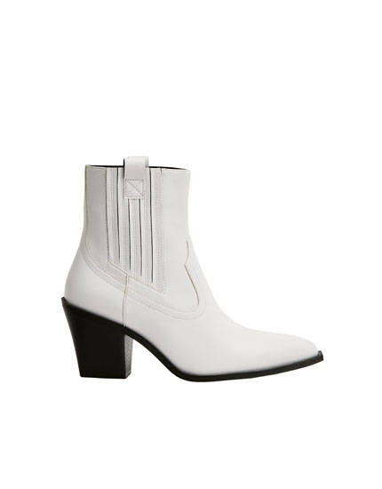 White cowboy ankle boots with glossy finish