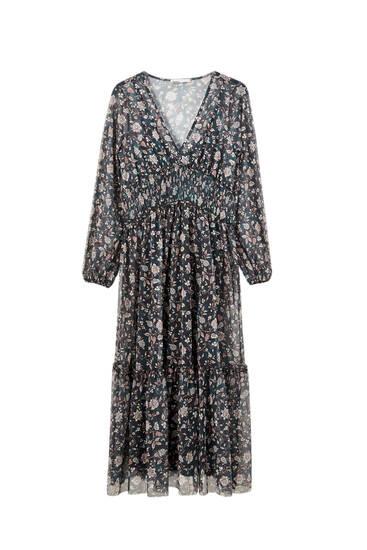 Удлиненное платье из полупрозрачной ткани с цветочным принтом.