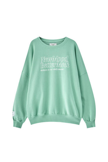 Green sweatshirt with white slogan