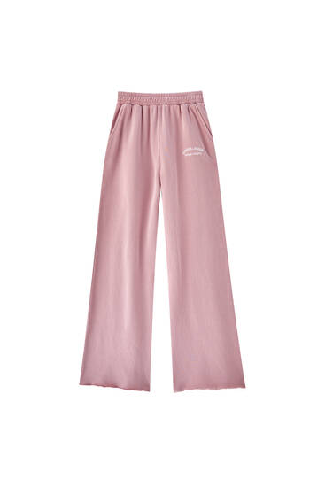 Pink jogging trousers with embroidered slogan