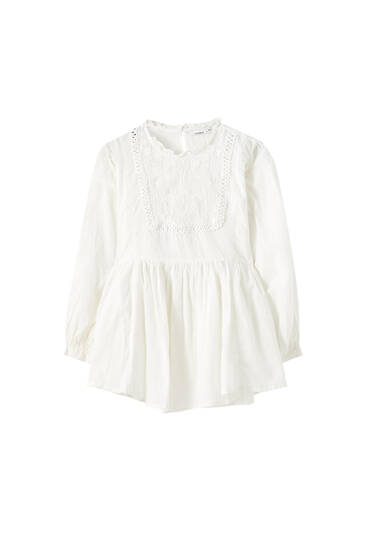White oversize blouse with an embroidered bib