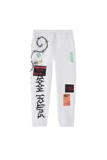 White jogging trousers with label print