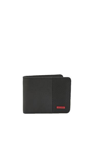 Svart plånbok med röd etikett